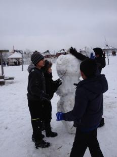 Boys having fun making their huge snowman!
